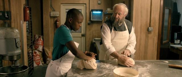 Jerome Holder and Jonathan Pryce bake — not break — bread together in Dough. Courtesy of Menemsha Films